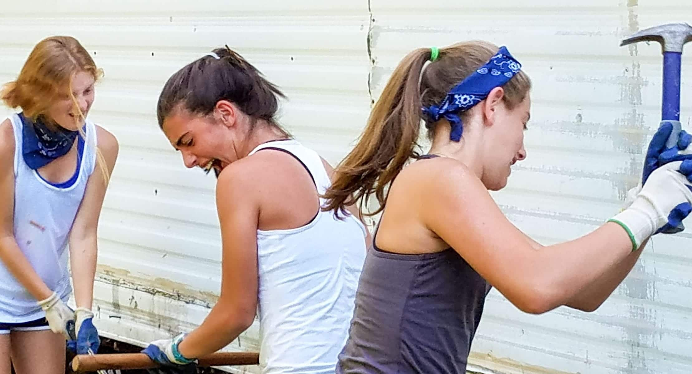three young women hitting hammers against a house