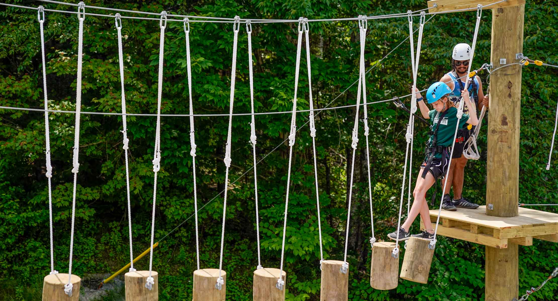 girl walking across cut logs in the air on an aerial rope course