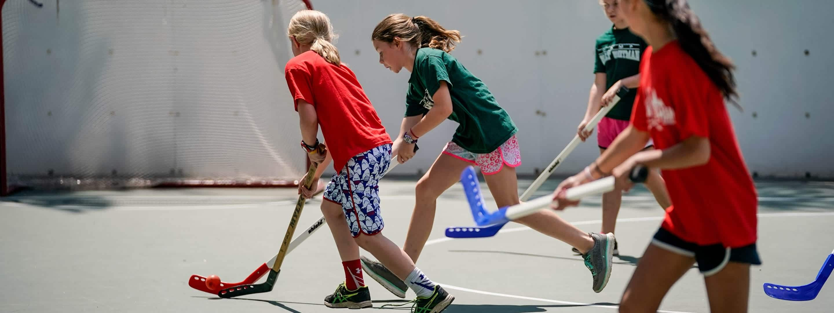 girls playing street hockey