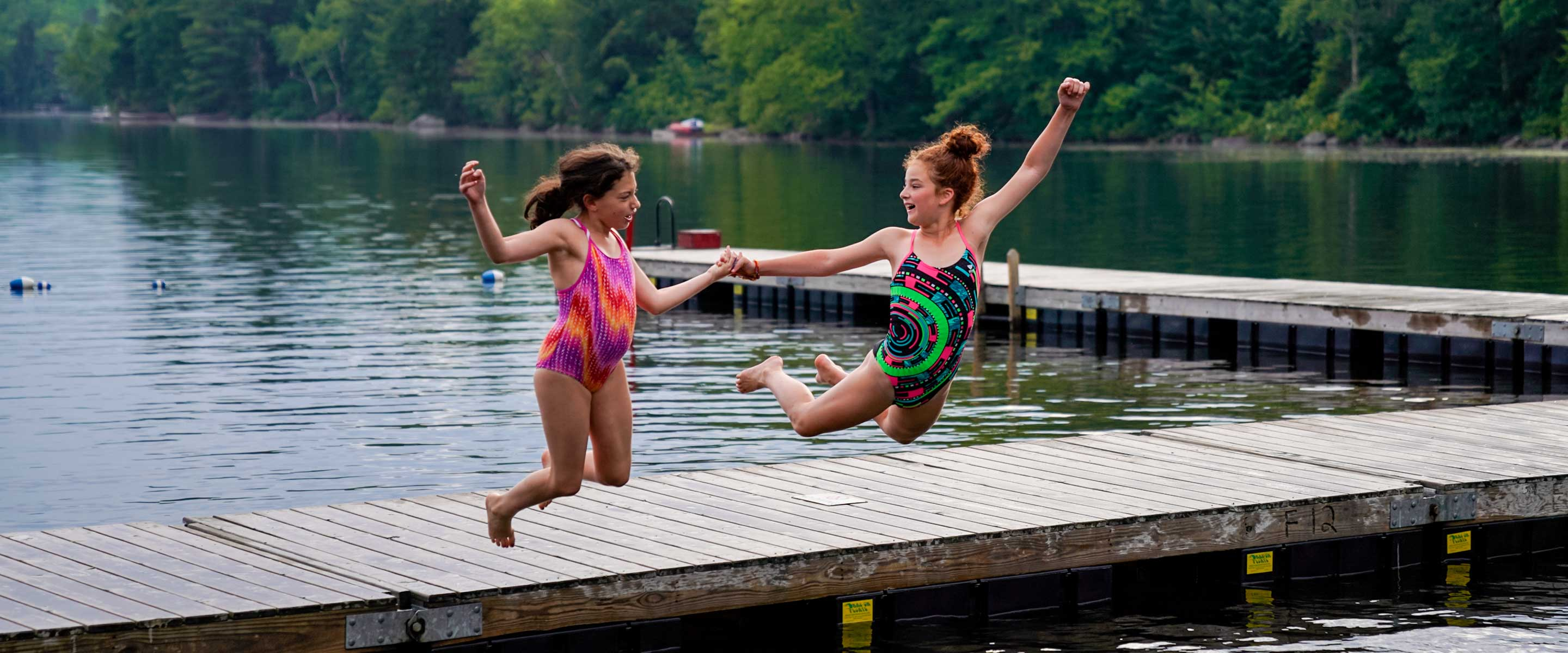 two young girls jumping into the lake from a dock