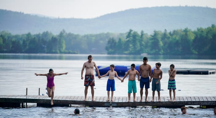 a group of campers on a dock with one girl jumping in