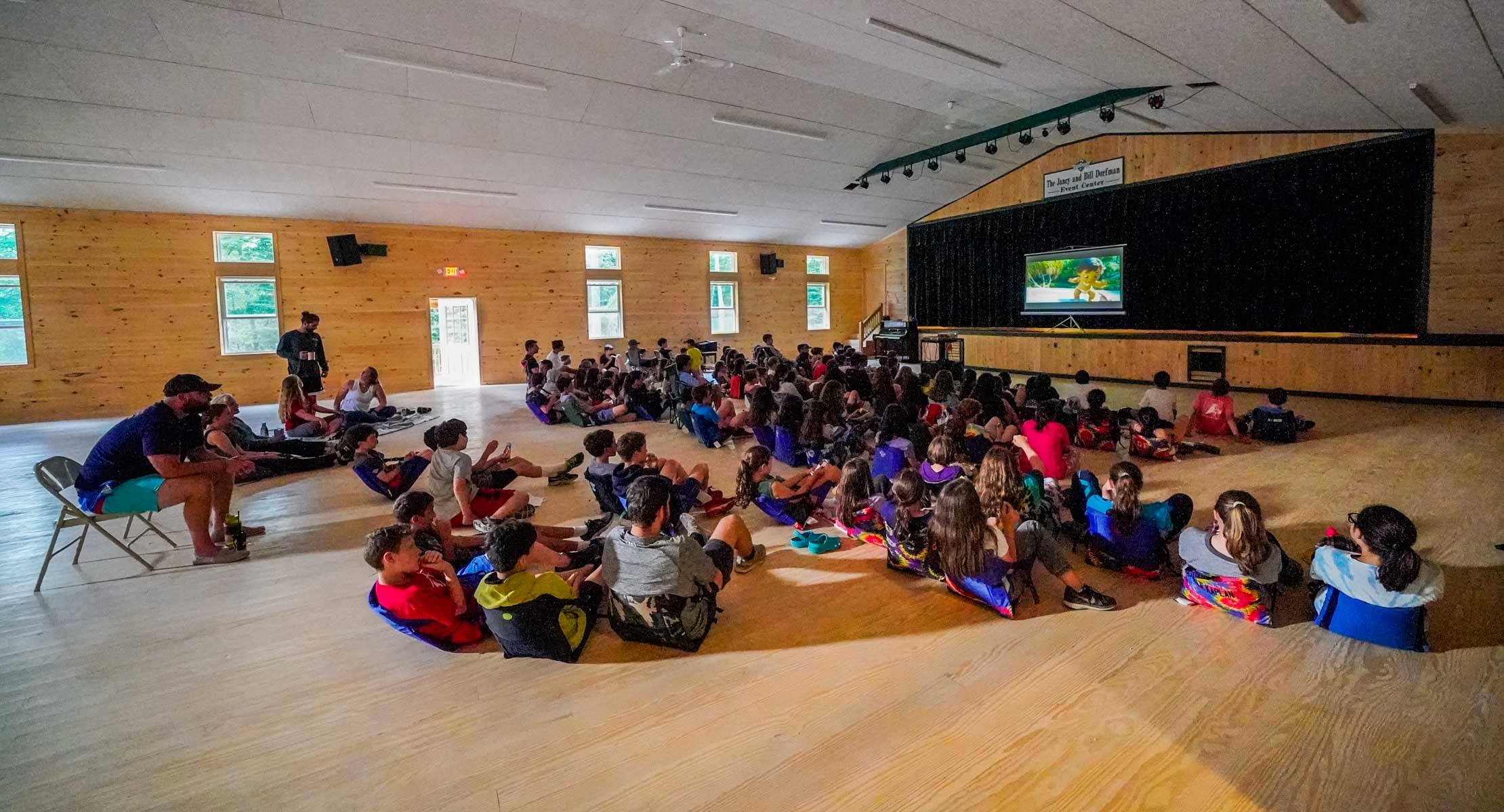 group of campers on the floor watching a movie