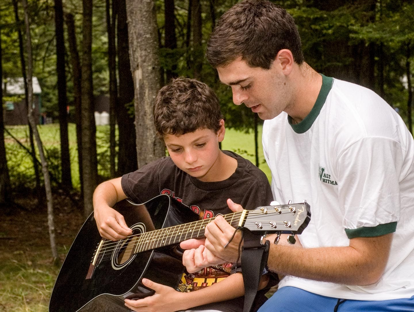 an instructor teaching a camper the guitar notes