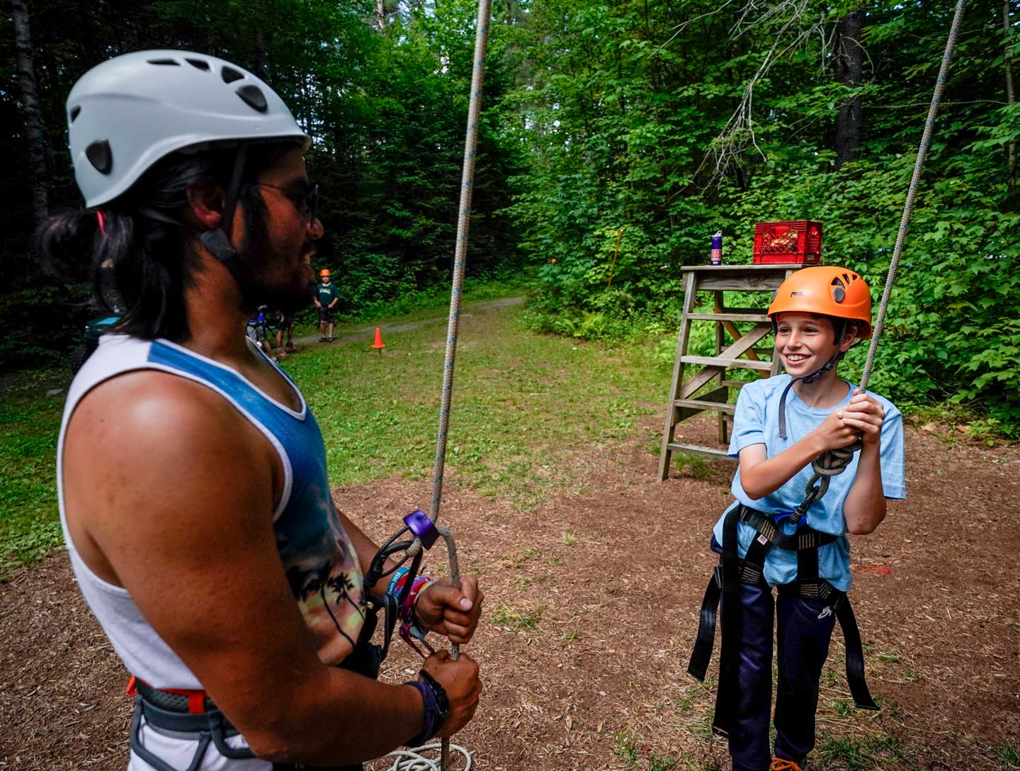 a camper and an instructor prepares for rock climbing