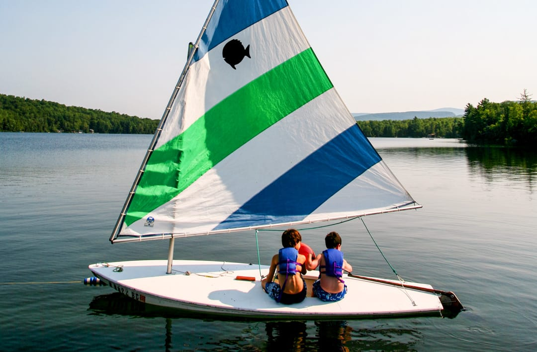 two boys on a sail boat on a calm lake