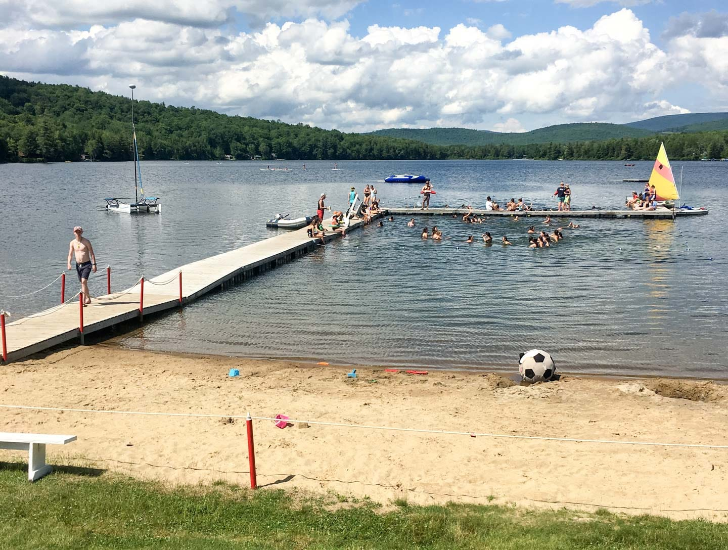 dock of a lake with a bunch of campers playing in water