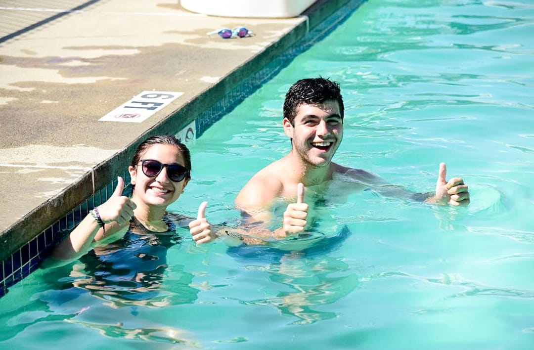 two people in a swimming pool giving thumbs up