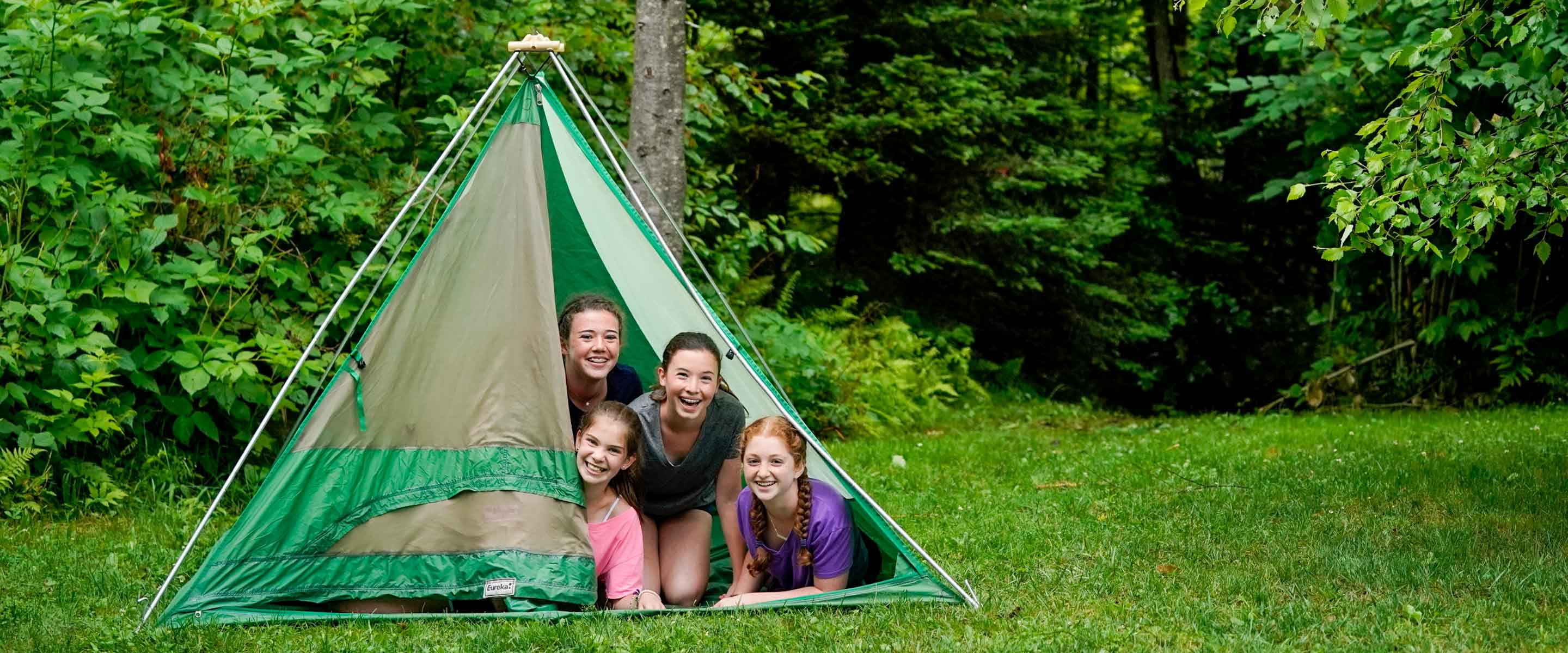 four girls peaking out from a tent
