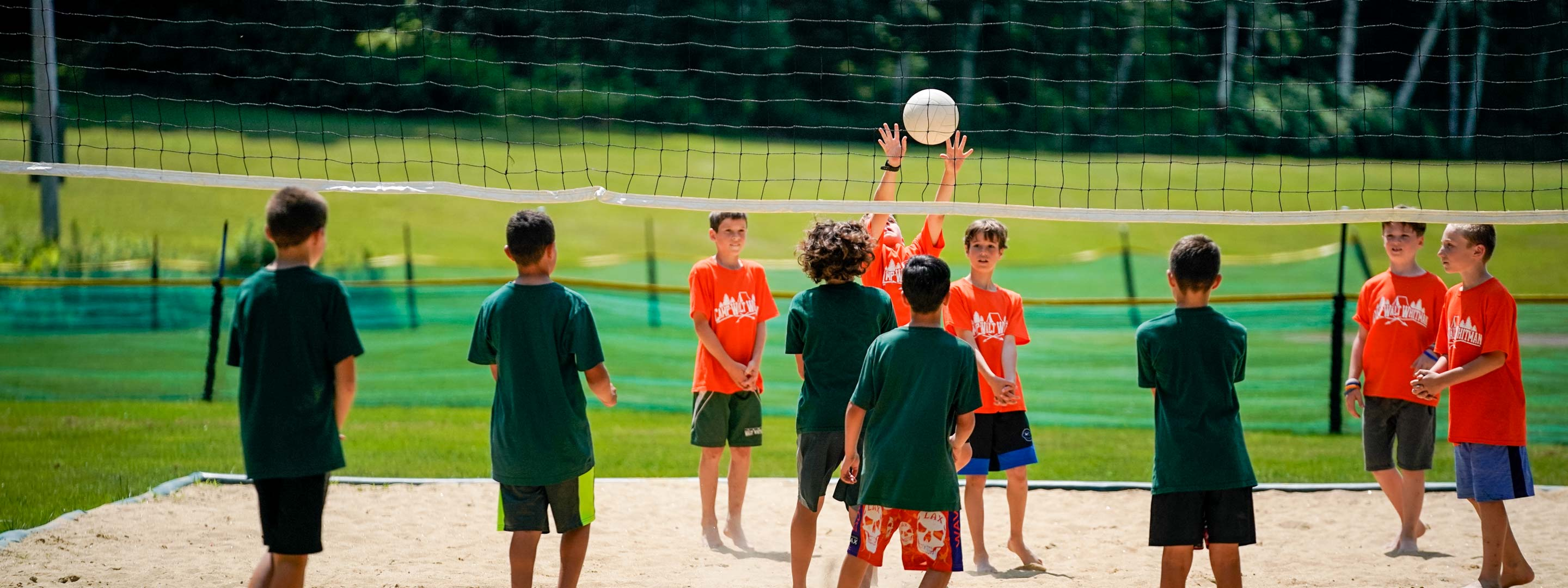 campers trying to play volleyball on a sand court