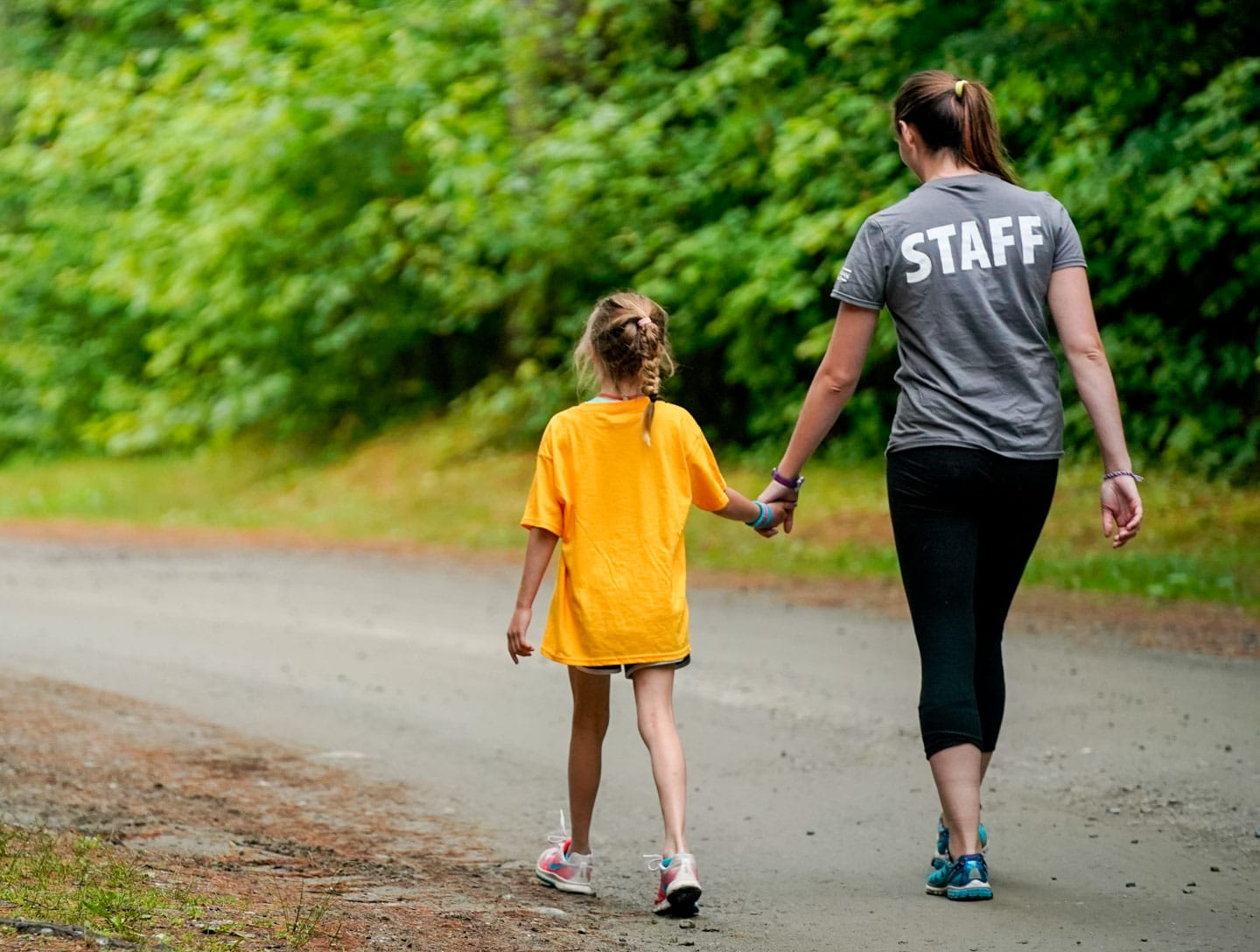 a young camper and a counselor walking down the road holding hands