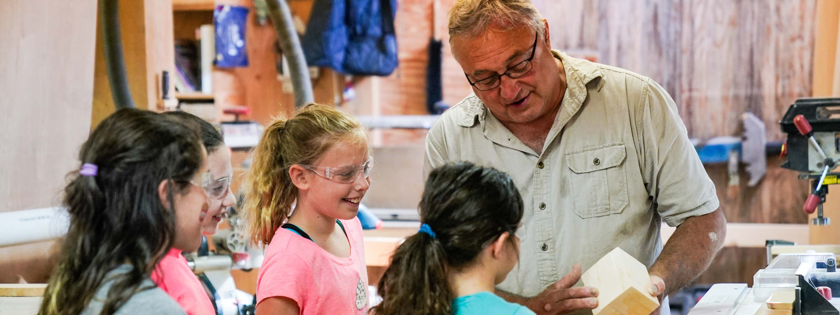 a man showing young girls a piece of wood