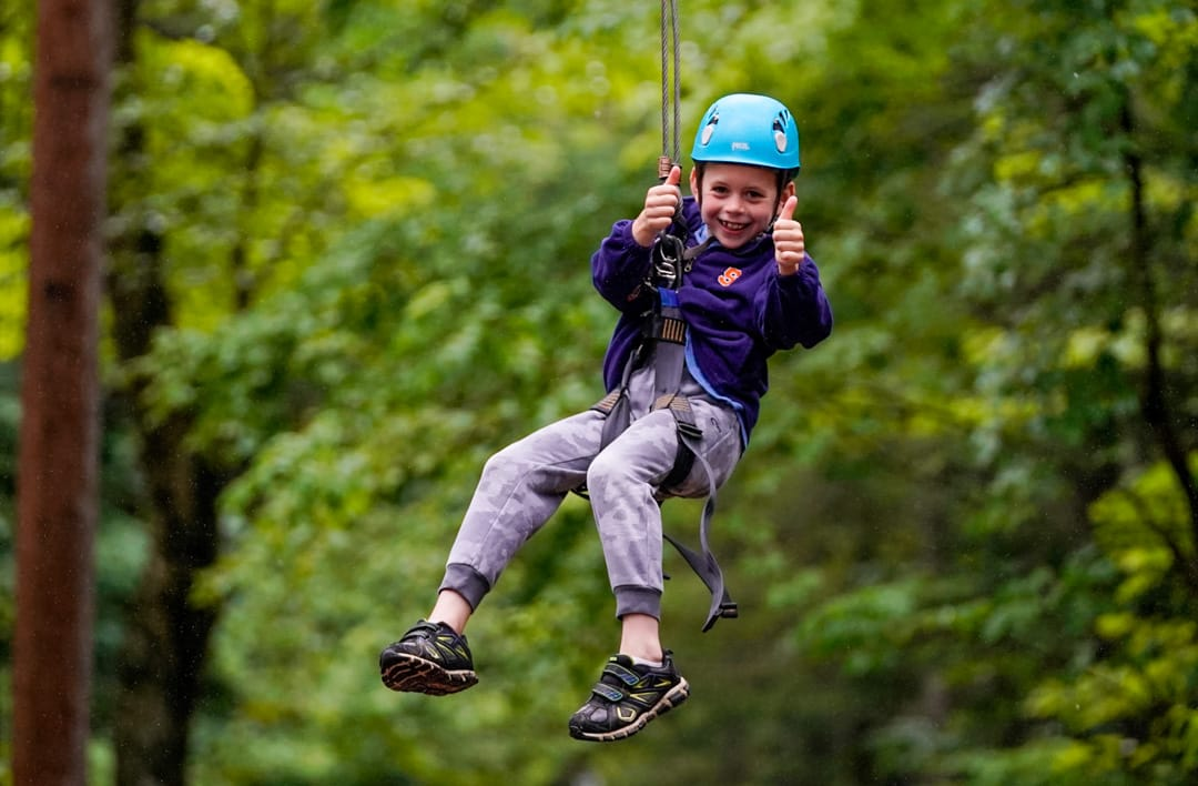 young girl ziplining and giving a thumbs up