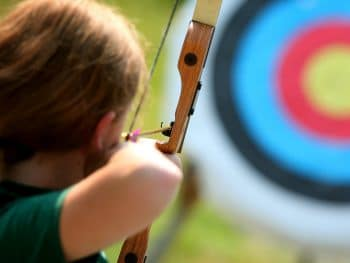 girl shooting an arrow at an archery target