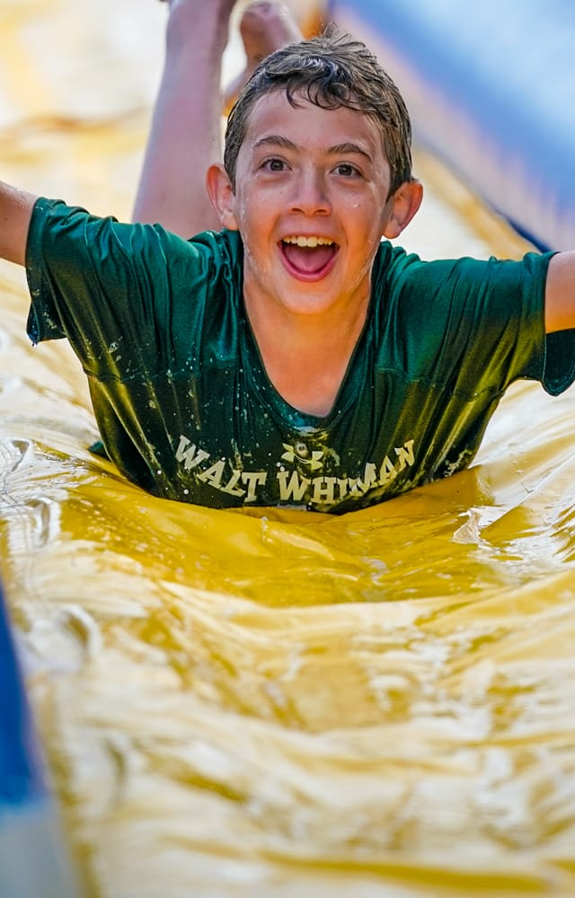 boy smiling with wide arms while sliding down a slip and slide