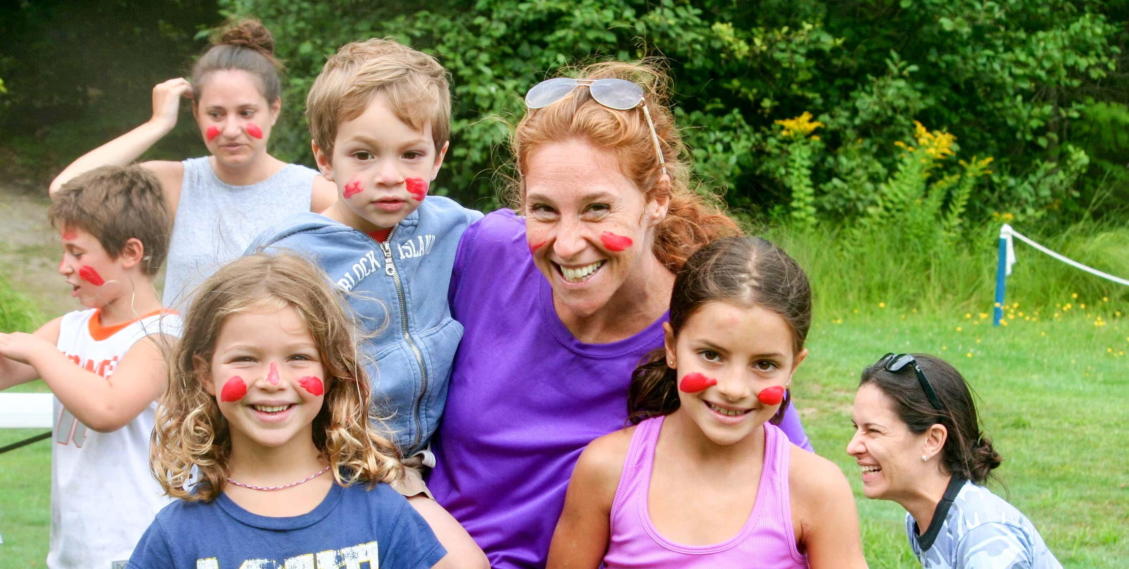young campers and a red-headed woman with red paint on their faces