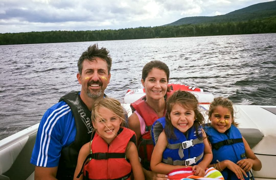 family with three kids on a boat on a lake