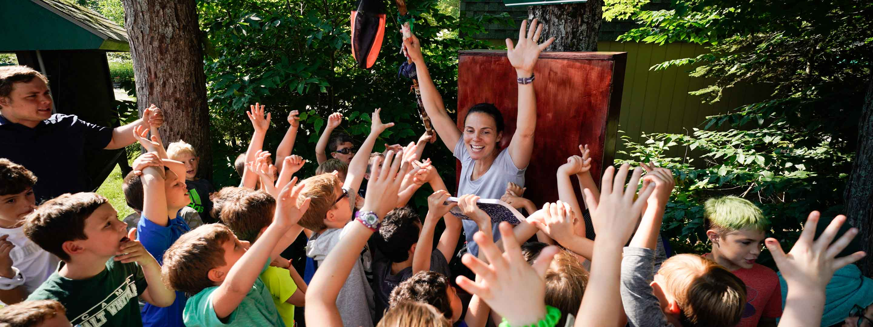 a counselor raising her hands while campers are around her with raised hands