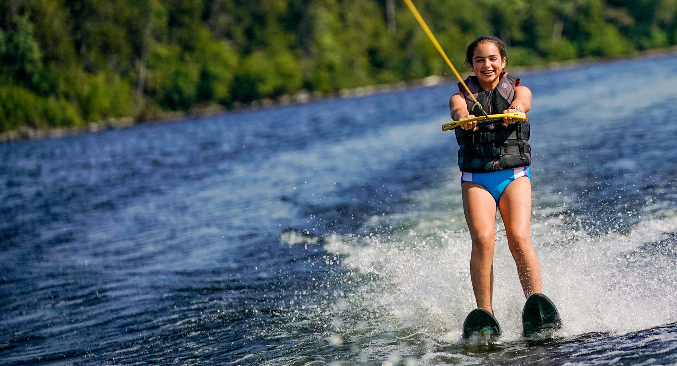 young girl smiling while water skiing