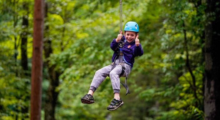 a young camper ziplining and giving a thumbs up