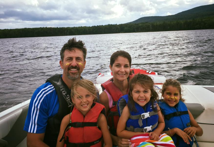 family of 5 smiling on a boat on a lake