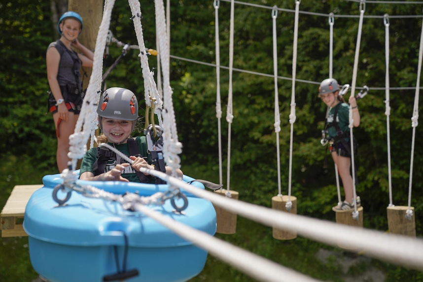 three girls having fun on an aerial ropes course