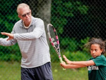 man teaching young girl tennis swing
