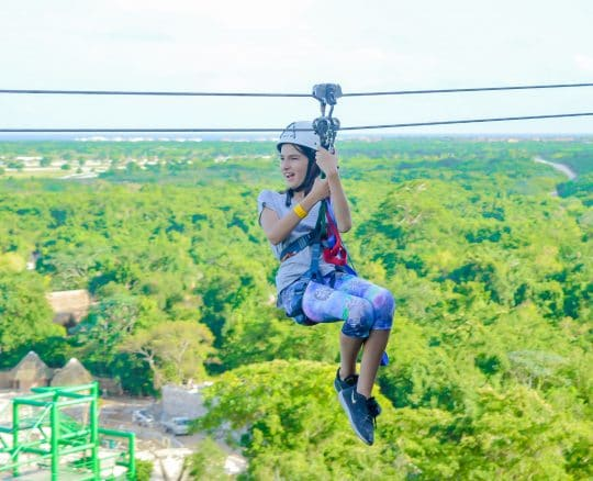 a girl smiling while ziplining across a background of green trees