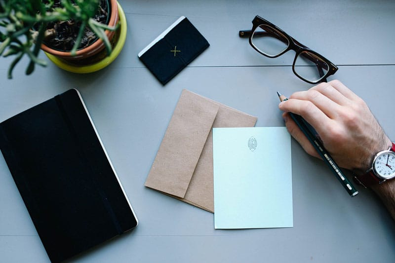 stock image of a card, a man's hand with a pencil, a notebook, business card, glasses, and a plant