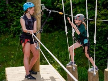 a young girl climbs on the tops of logs while another girl watches