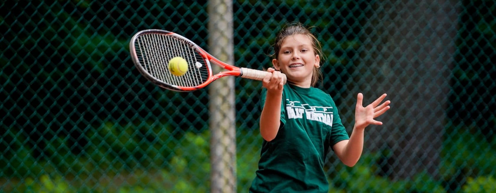a girl swings her tennis rackets and hits a ball