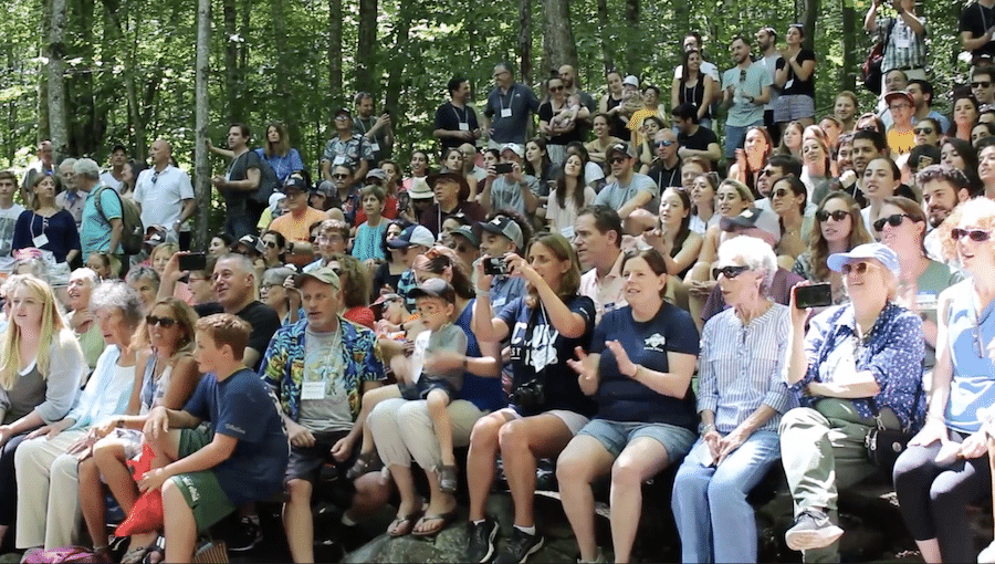 a group of parents sitting, many holding cameras up