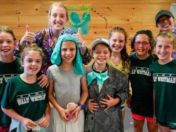 a smiling group of young girl campers with two counselors