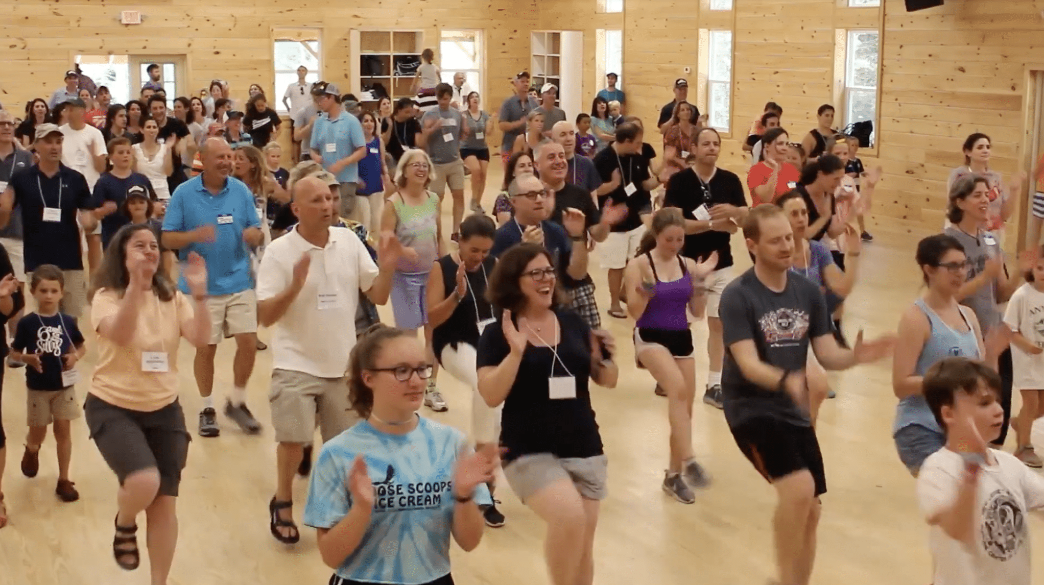 a group of counselors and campers dancing and clapping together