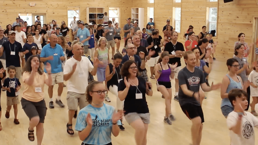 a group of adults and young campers dancing and clapping together