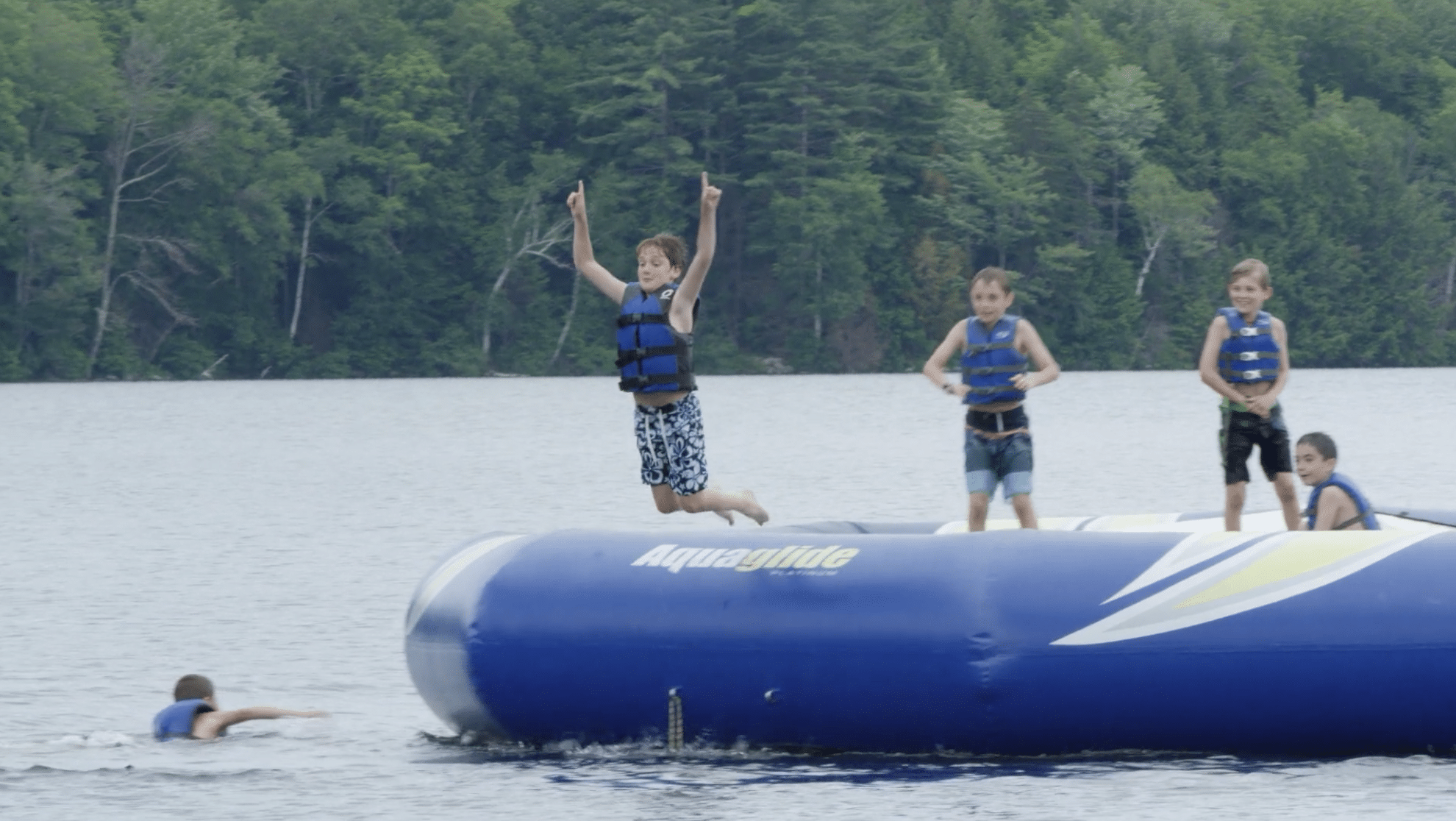 a group of young boys bouncing off an inflatable into a lake