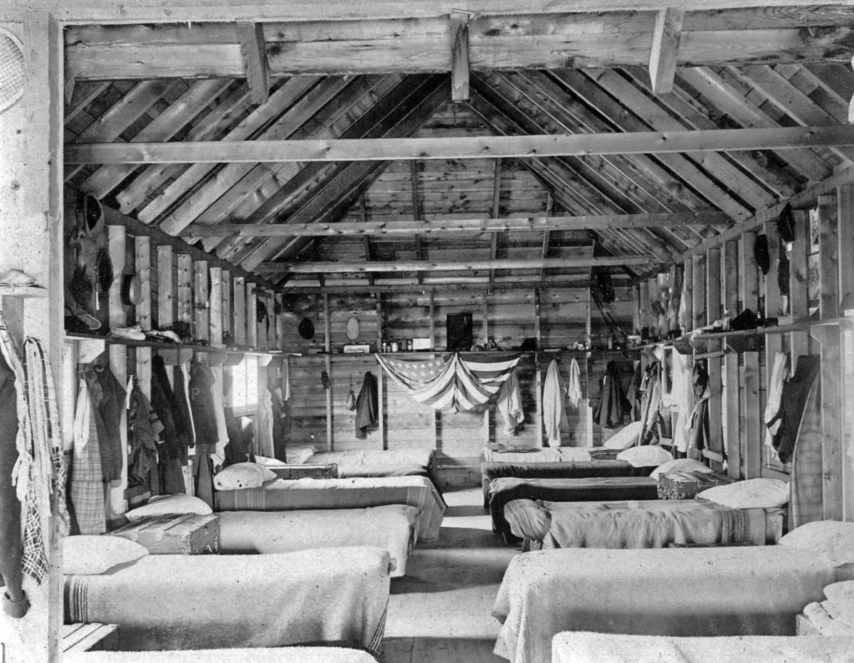 black and white photo of old fashion cabin with beds and an american flag