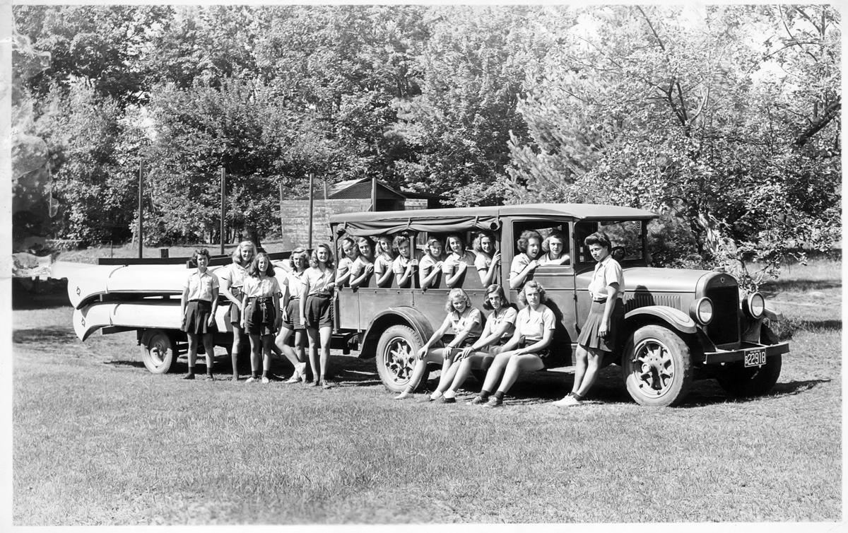 a black and white photo of a group of women standing next to and sitting in a long car that's towing canoes