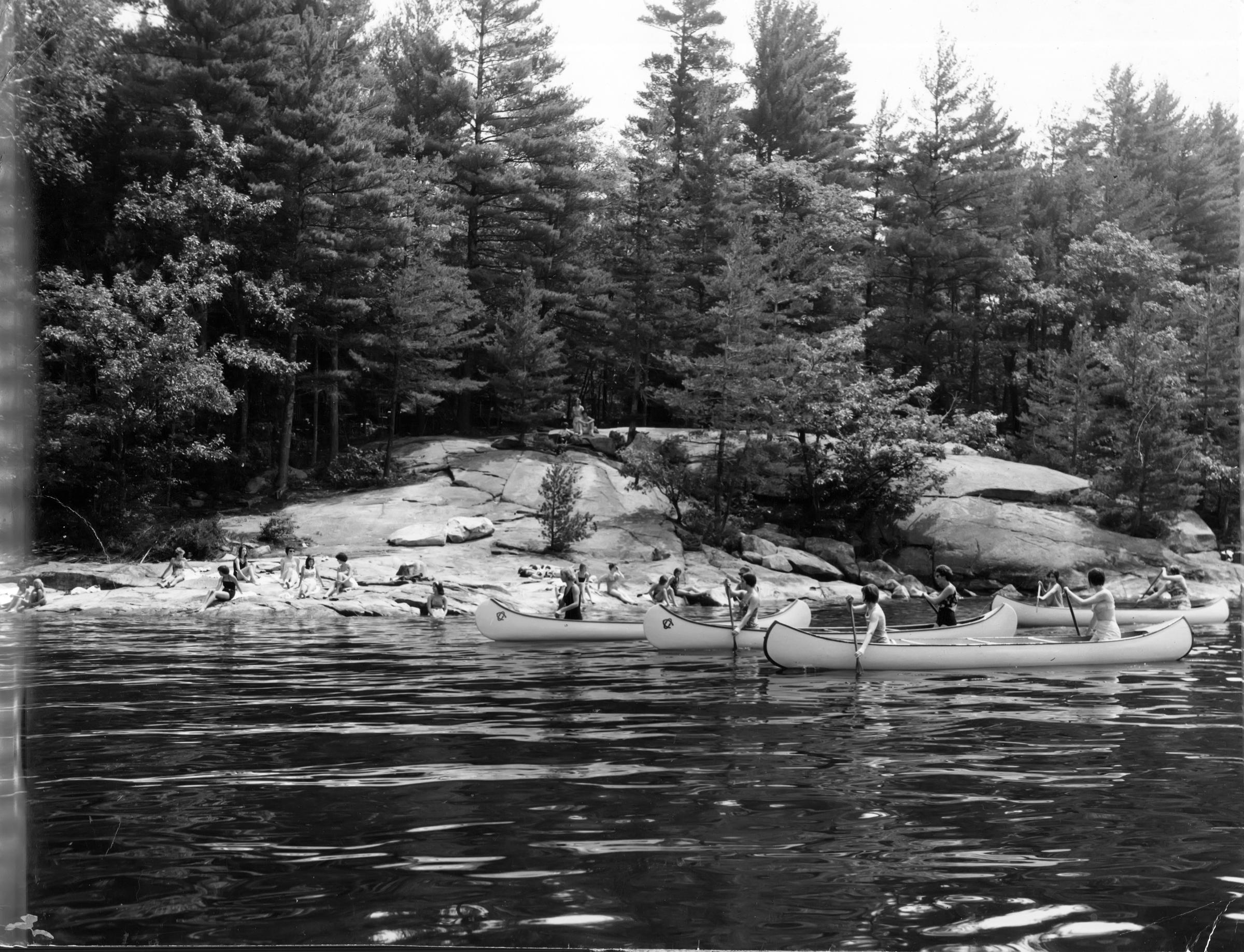 black and white photo of women paddling canoes on a lake and relaxing on a rock