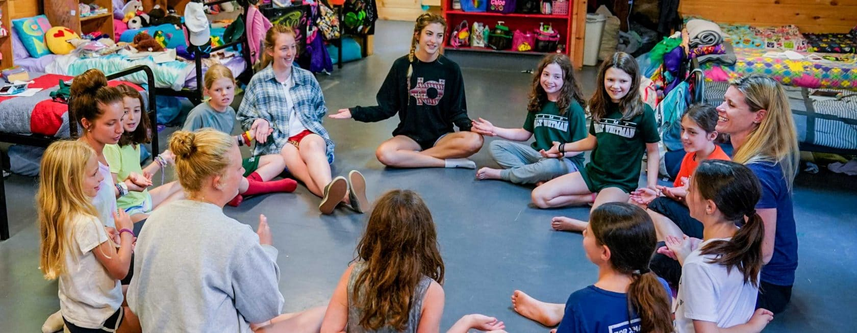 group of campers and counselors in a circling playing a game