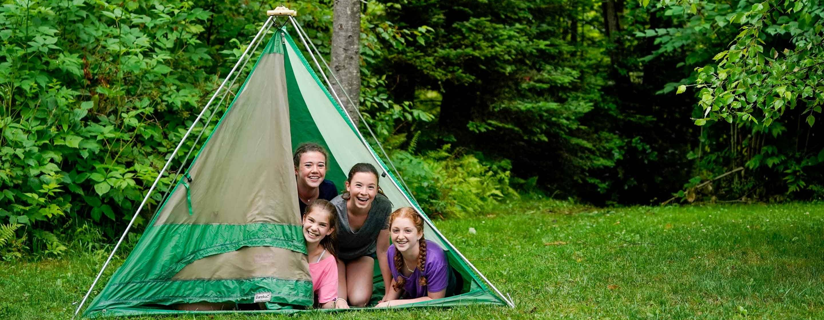 4 young girls peaking out from a tent in a forest