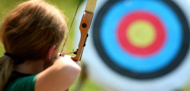 young girl with an arrow drawn back about to shoot at an archery target