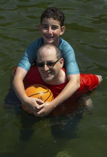 Father and son playing in the lake at Camp Walt Whitman