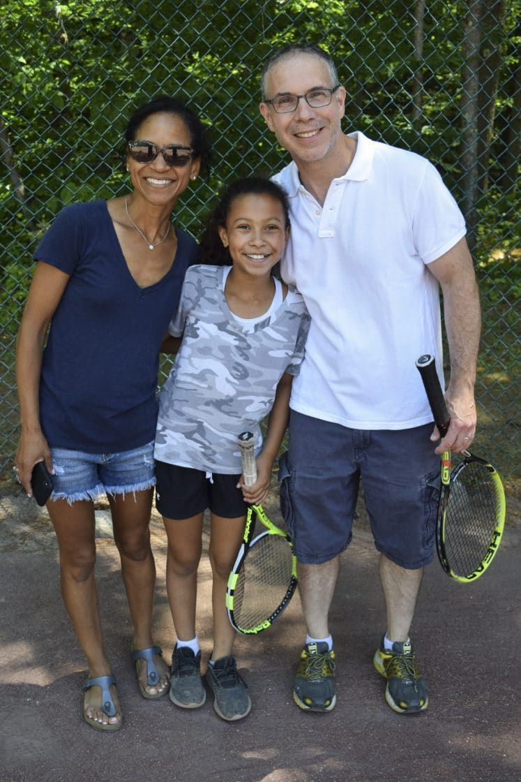 Family playing tennis during visiting day at Camp Walt Whitman