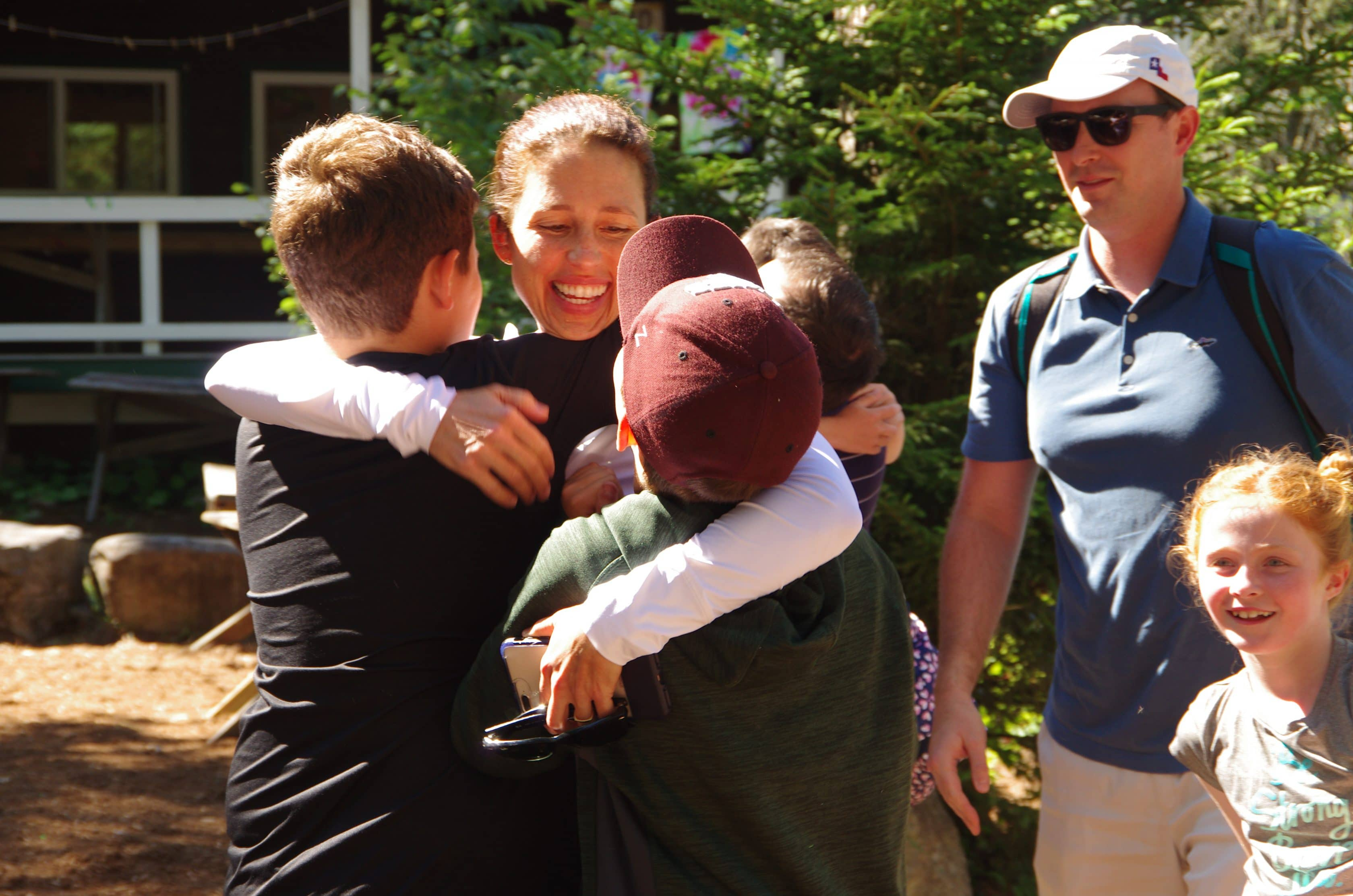 mom hugging her boys during visiting day at Camp Walt Whitman