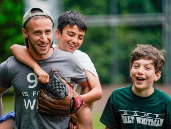 camp counselor with campers on baseball field