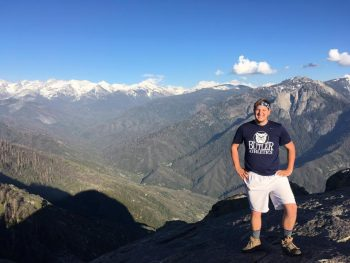 Man posing with mountains in the background